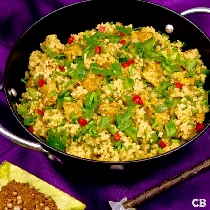 Maaltijdsalade van kruidige couscous met gemarineerde kipblokjes en groene paprika