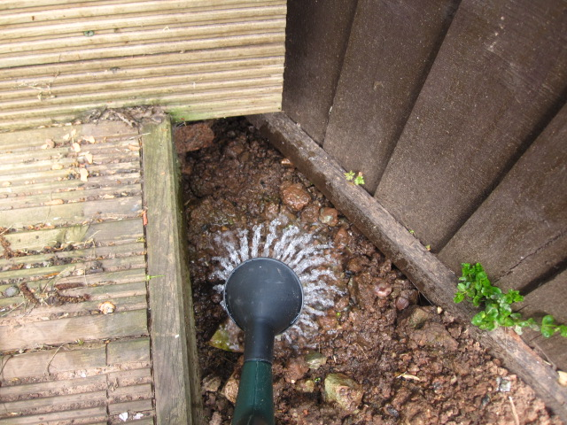 A watering can being used to wet the soil