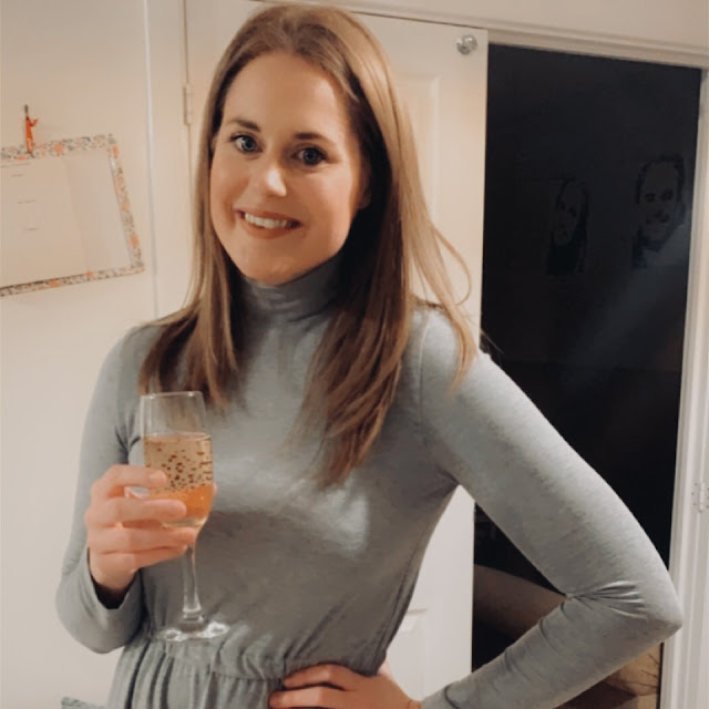 Girl smiling holding a glass of sparkling rose