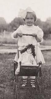 Foto antigua de niña con cochecito antiguo
