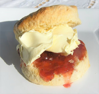 Scottish teatime scone filled with cream and strawberry jam