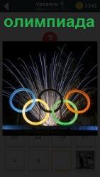 На фоне фейерверка кольца олимпиады, из - за которых фейерверк в разные стороны