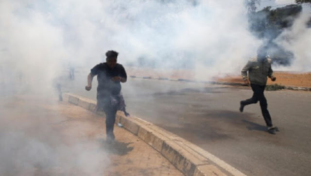 Police in Kakamega run teargas canisters hurled on them during curfew hours.