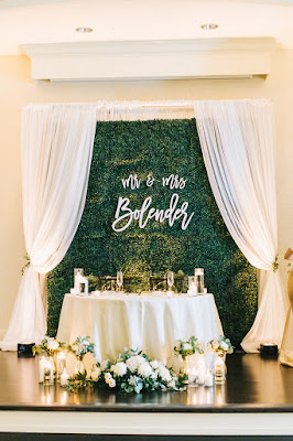 sweetheart table flowers and hedge wall with name