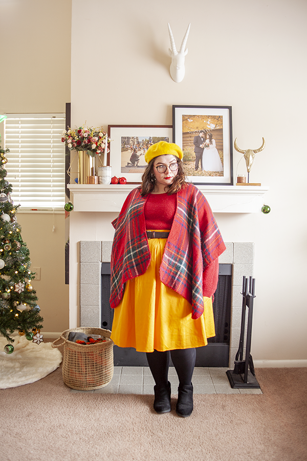 An outfit consisting of yellow beret, red shawl over a red sweater tucked into a yellow midi skirt and black ankle boots.