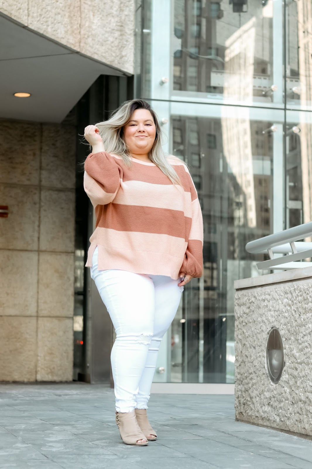 Chicago Plus Size Petite Fashion Blogger, influencer, YouTuber, and model Natalie Craig, of Natalie in the City, reviews Chic Soul's white skinny jeans and a striped sweater.
