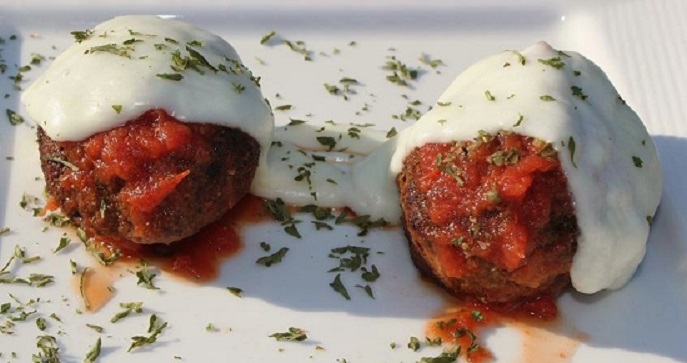 these are chicken parmesan meatballs made with ground chicken topped with melted mozzarella cheese in a rich tomato Italian sauce