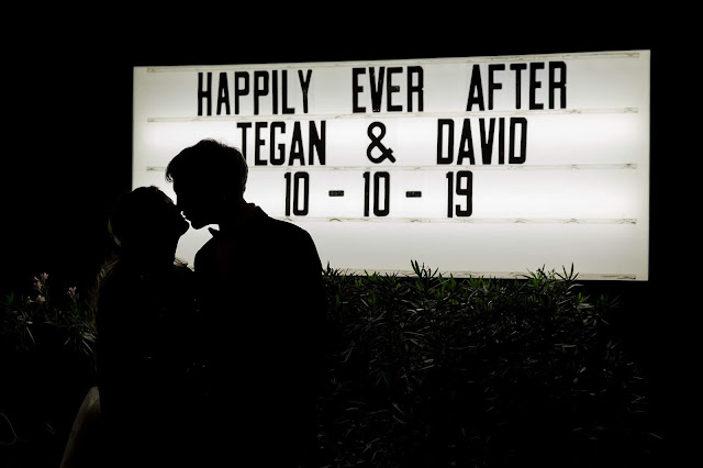 Shenandoah Mill in Gilbert AZ Wedding Photo of the bride and groom silhouette at a marquee sign by Micah Carling Photography