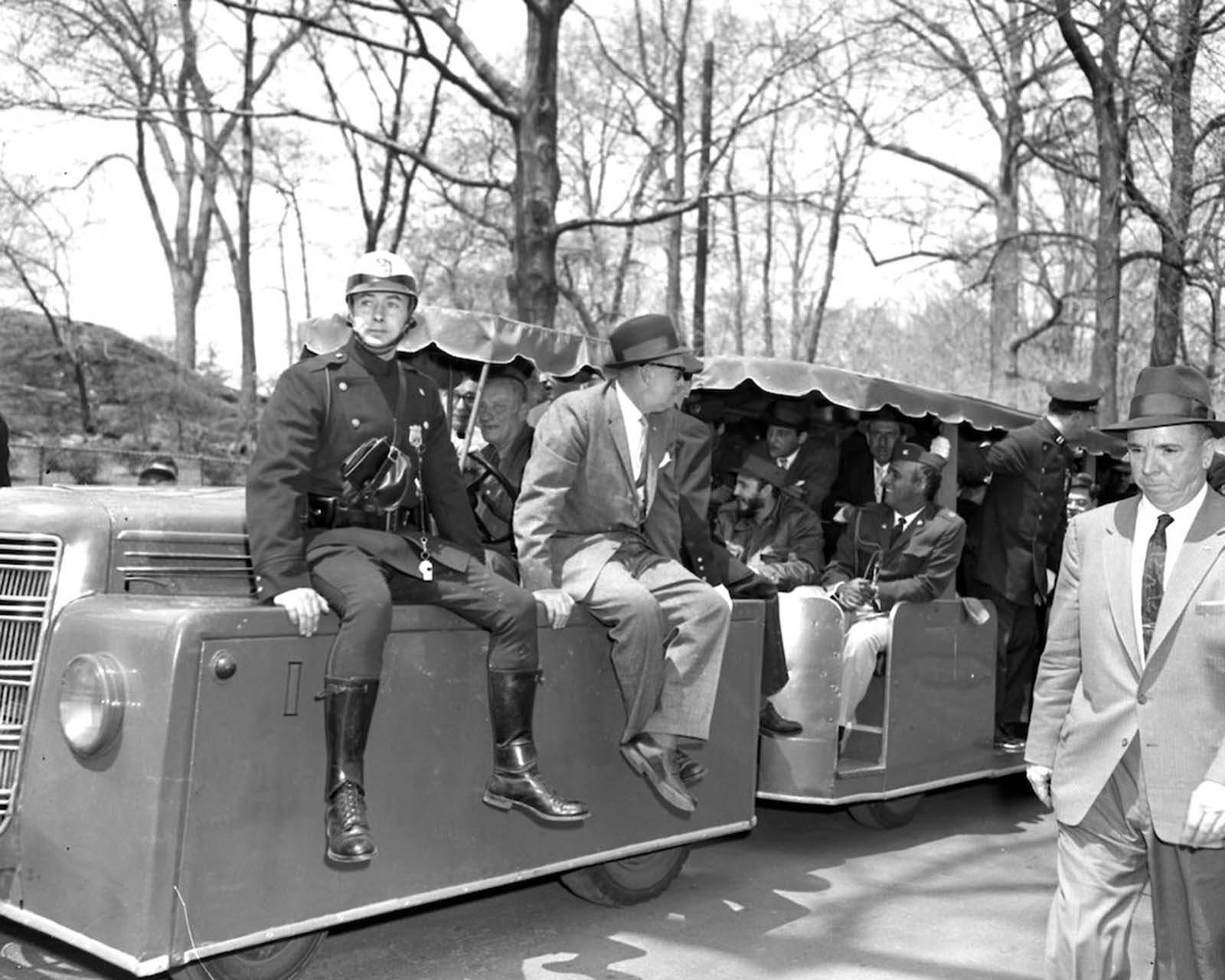 Police and plainclothes detectives ride the miniature railway transporting Fidel Castro during his tour of the Bronx Zoo.