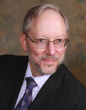 Professional headshot of a very distinguished-looking older white man with a balding grey pate, neatly trimmed grey beard, and wire-rim eyeglasses