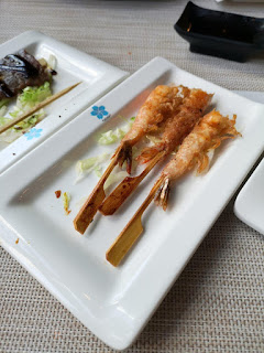A white rectangular plate with dark rectangular strips of sushi with two thin light brown chopsticks on either side on a white rectangular plate on a bright background