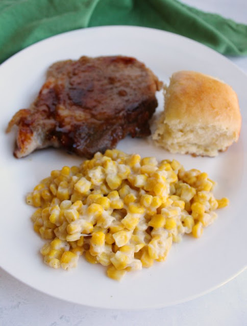 dinner plate with hawaiian roll, parmesan corn and braised pork chops
