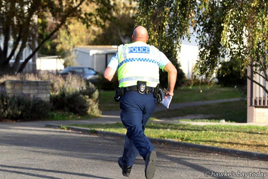 A policeman runs onto the property after a man was heard yelling loudly - St John Ambulance and police attended an incident outside a block of flats in Karamu Rd South, Hastings, where witnesses said a man was injured when a woman drove a car into him. A man was taken to Hawke's Bay Hospital and police escorted a woman from the property.  photograph