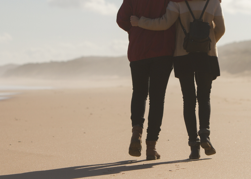 A couple walking along the beach in a blog post about simple ways to create lasting memories with your partner.