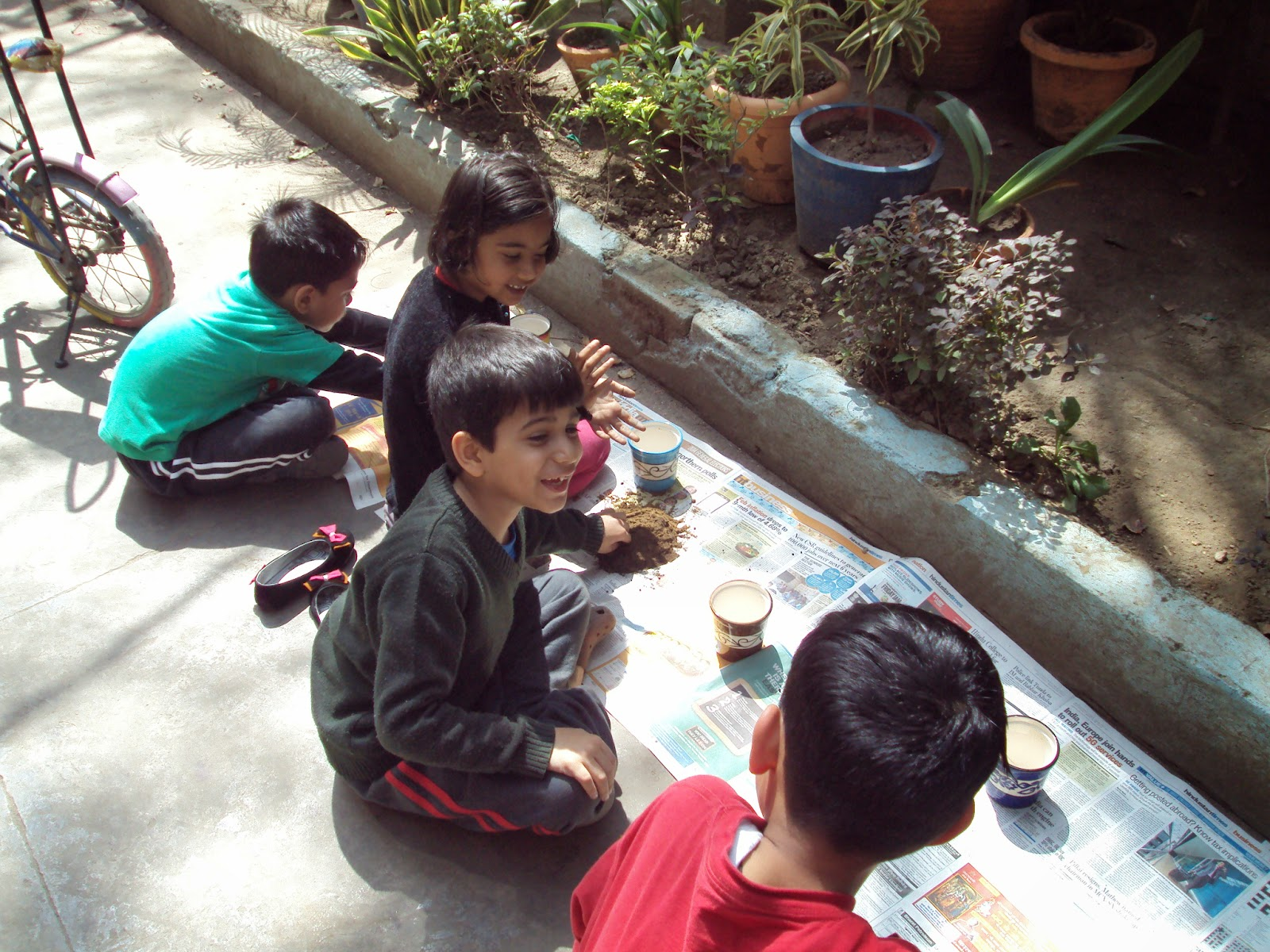 Introducing Young Ones to the Art of Gardening || 'Pot a Plant' Activity. One doesn't always have to plan forever to attain good results, and this is what my sister and I discovered when we conducted a 'Pot a Plant' session for the kids in our colony. We had been talking about this since last year, but when it came to the actual planning and prep work, it barely took us one hour to put it all together - right from collecting the material required, planning the session, inviting the kids, and setting up the venue.Even though the idea came to us almost one year back when I and my sister were talking about doing something apart from our regular work and outside our schedules, we made a decision about the venue, date, content, and participants of the activity in a matter of seconds when we were walking around the gardening shops at the Garden Tourism Festival 2014 organized by Delhi Tourism. We bought 10 little ceramic pots - bright and colourful. And after that everything simply fell into place. We decided upon the weekend - 16 March 2014, Sunday - just one day before Holi, and the venue would be our locality in Rohini. The session would be conducted at around 11 am, which won't be too early for the kids, nor too late so that their families could still utilize the rest of the day for any other outing they plan to do. We decided that we would take the kids through the simplest possible process of potting a plant. The saplings that would be potted should be attractive to the kids, and should give gratifying results in a short period of time. In other words, something that would flower early. So we zeroed in on Portulaca Grandiflora, commonly known as the 10 o' clock plant because its flowers bloom at around that time and close within a couple of hours. It took us half an hour to go pick up the saplings, compost, and soil from our local nursery, and a further 15 minutes to pick up fruit juice and snacks for the kids, so that they can re-energise themselves after working hard in the garden. And once everything was set, we sent out the invitations to the kids - mostly my nephew's friends between 6 to 9 years of age. We invited 9 kids and then we could only sit and wait for the time to arrive - our exciting increasing with each passing minute. We were hoping that the children would also be as excited as us. And we were happy to see almost all kids arrive at the venue 10 minutes before time and waiting for us to start the activity. We had invited 9, but 12 arrived. We had to drill holes in three ceramic glasses from our kitchen and give them to the kids that arrived last. Because of their punctuality, we were able to start dot on time. We started with talking about why it is important to have plants around us and then asking the kids whether any of them have ever potted a plant. Some of them had done it for some school projects, but most of the kids were new to this. We told them about Pots, crocks (little pieces of broken pots placed above the hole at the bottom to help with drainage of excess water), watering can, soil, and compost, and were delighted by their enthusiasm, interest, attentiveness, and quick grasp. When it came to the practicals, the kids were required to stand in queues several times and demonstrate a lot of patience. Not one of them tried to break the queue. They observed carefully and executed perfectly. The only complain we heard from them was about the smell of compost. By the end of it, all kids had selected their favourite pots, placed crocks in them, mixed soil and compost, and planted the sapling. We then explained to them about the process of watering and how to decide when their plants needed water. We told them about the benefits of sunlight and the harms of overwatering. We also prepared them about the natural lifecycle of the plant, and told them that the plant would die at the end of summers and they should not feel disheartened when it did. The kids promised to take care of their plants and to let us know when the first flower blooms. Kids were happy and really charged up. All this while, they had been sitting on the ground and getting their hands dirty. Once they were done, they washed their hands properly with soap and grabbed their juices and snacks. They were highly protective of their plants and left us with cheerful goodbyes, their faces glowing. Once they had left, we realized that several people had been looking down from their windows and observing us and the kids. One of them shouted