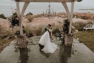 Pareja de novios besándose bajo el arco de la ceremonia de boda