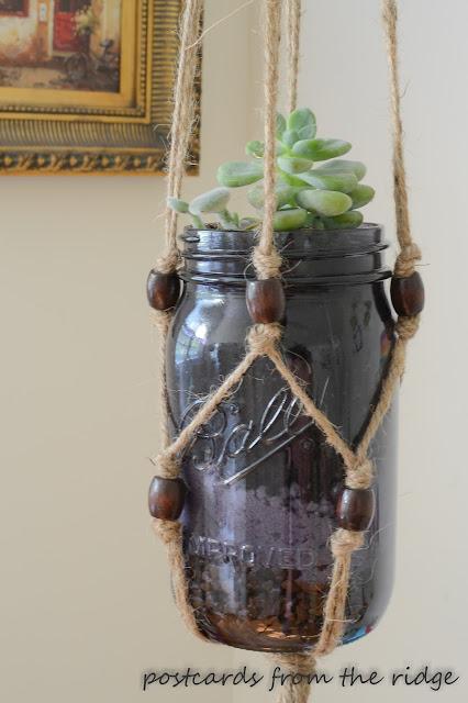 succulent in purple mason jar and macrame plant holder
