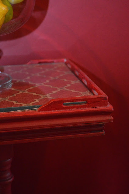 The corner of a red painted table with glass top