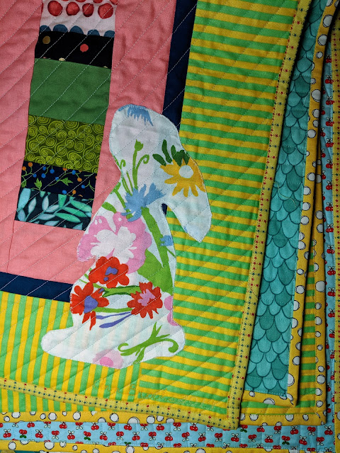 The folded quilt shows the  of rabbit on the front, portions of the back, and yellow print binding.