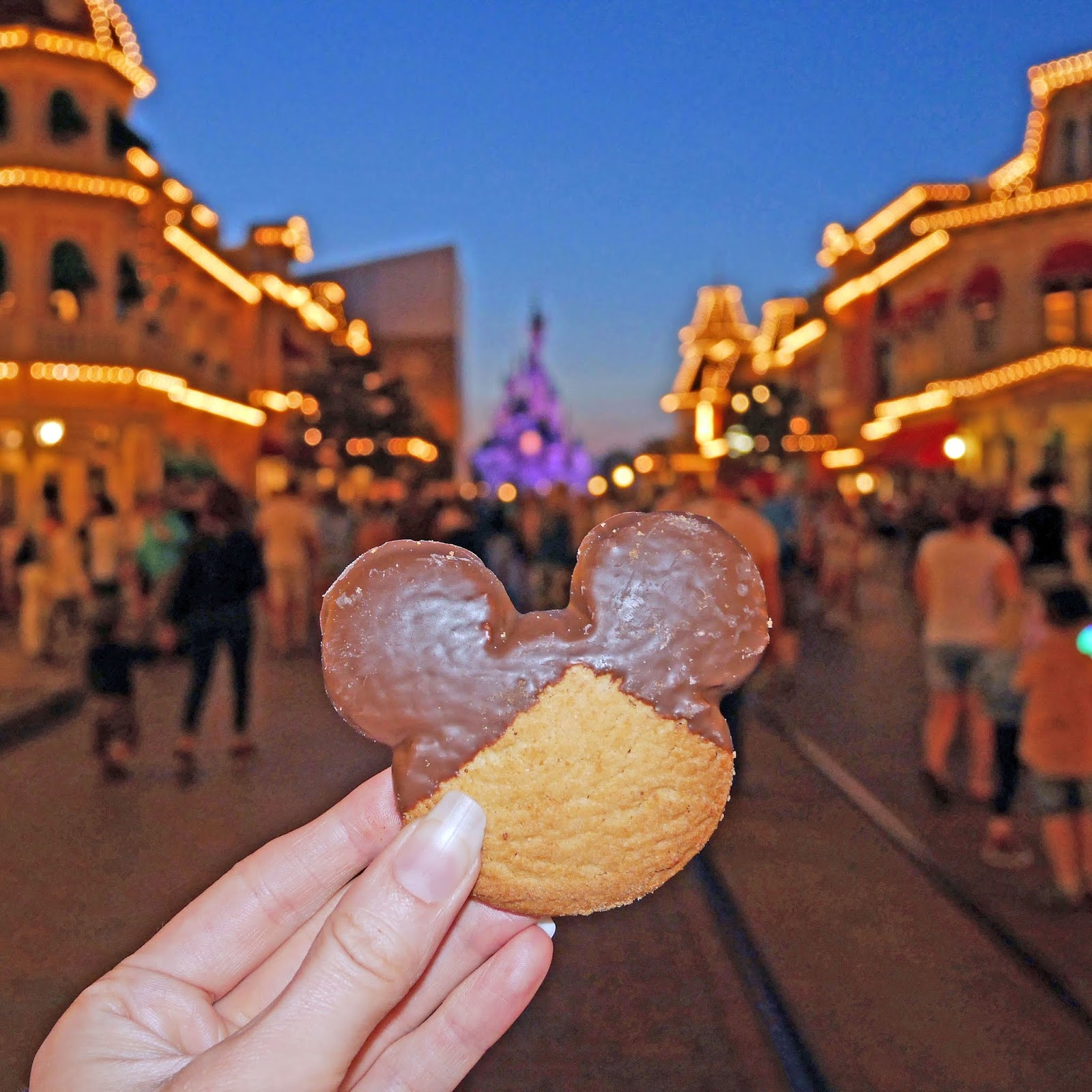 Eating a Mickey Mouse cookie on Main Street USA during the evening