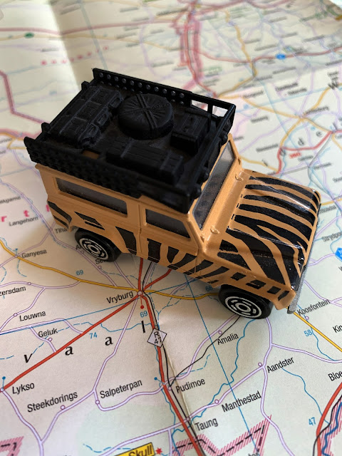 A beige and black painted ty Land Rover parked on a paper map next to the words Vryburg.