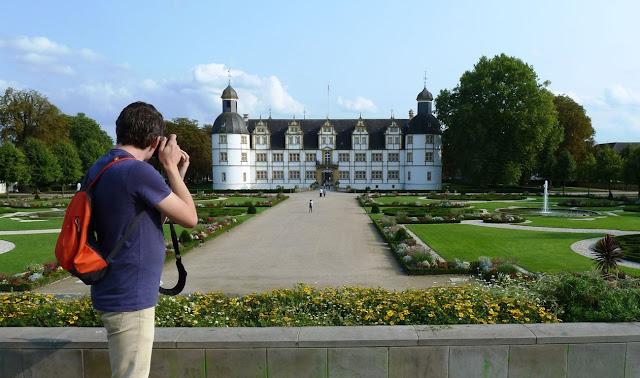 Im Vordergrund Timo, der ein Foto vom Schloss und dem Schlossgarten im Hintergrund macht.