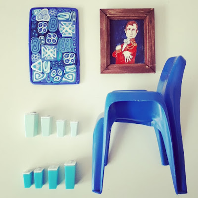 Flat lay of one-twelfth modern miniature items in blue and white, including a painted portrait, a wall piece, a Sebel plastic chair, and retro kitchen containers