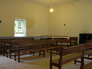 A magnolia-painted meeting room with one small window, and several rows of traditional wooden benches.