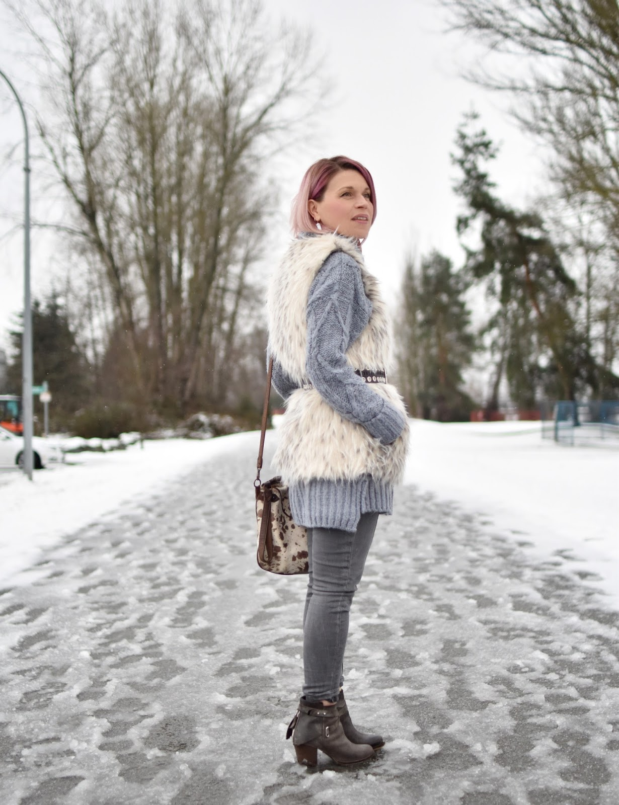 Monika Faulkner outfit inspiration - styling a tunic sweater with a belted faux-fur vest and grey skinny jeans