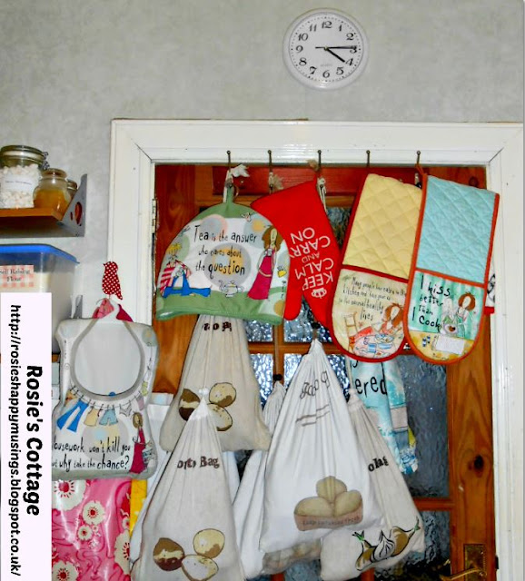 A Wooden Coat Hook Bar Attached To The Door Provides A Home For Assorted Hanging Vegetable Storage Bags, Tea Cosies & Oven Mits.