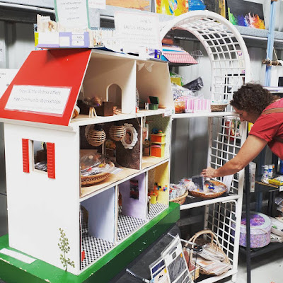 Child's wooden dolls' house filled with home-made furnishings, on display next to a shelving unti displaying baskets of craft items. A woman is looking through one of the baskets.