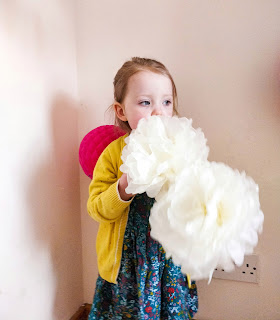 A blonde haired, blue eyed girl wearing a green floral dress and yellow cardigan is stood in front of a cream wall with two white fluffy paper flower balls held one in front of the other beside her mouth. There is a small honeycomb structured decoration ball in pink just behind her right shoulder.