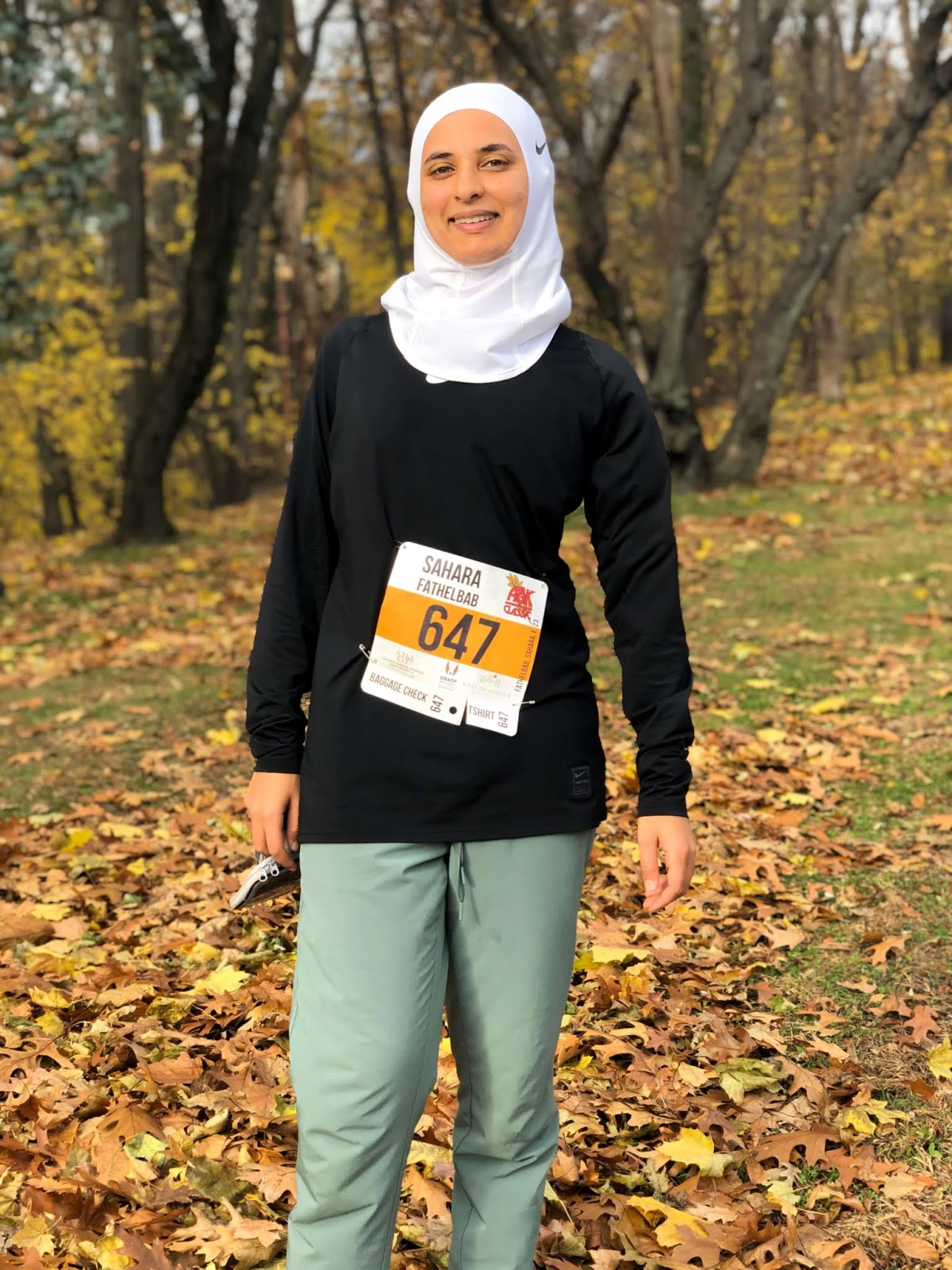 Sahara smiling after 8K race in white nike hijab and trees in the background