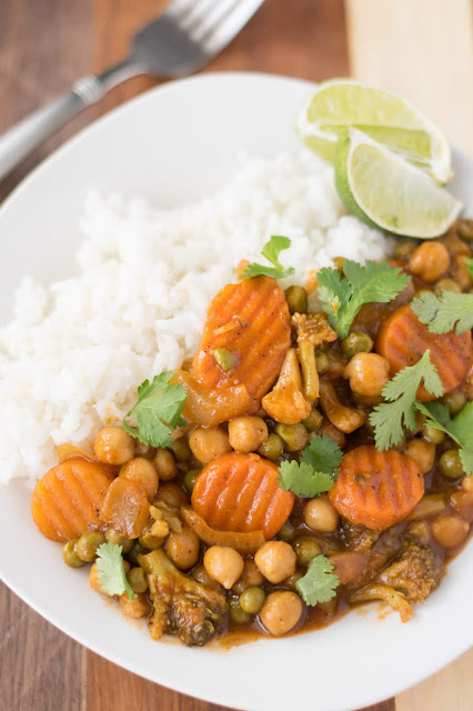 The finished plate of Easy Vegan Chickpea Curry Recipe on a white plate with some white rice, lime, and a fork.