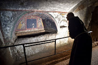 "A friar looks at a fresco, part of the ""dei Fornai"" (bakers) cubicle, during a visit after the restoration of the catacomb of Santa Domitilla, in central Rome, on May 30, 2017 [Credit: AFP/Andreas Solaro]"