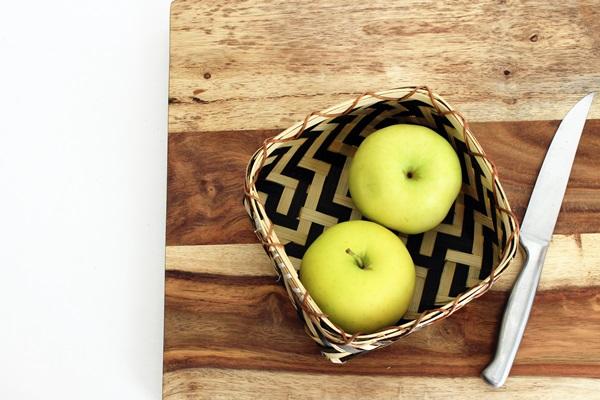 Duas maçãs dentro de uma cesta com uma faca ao lado