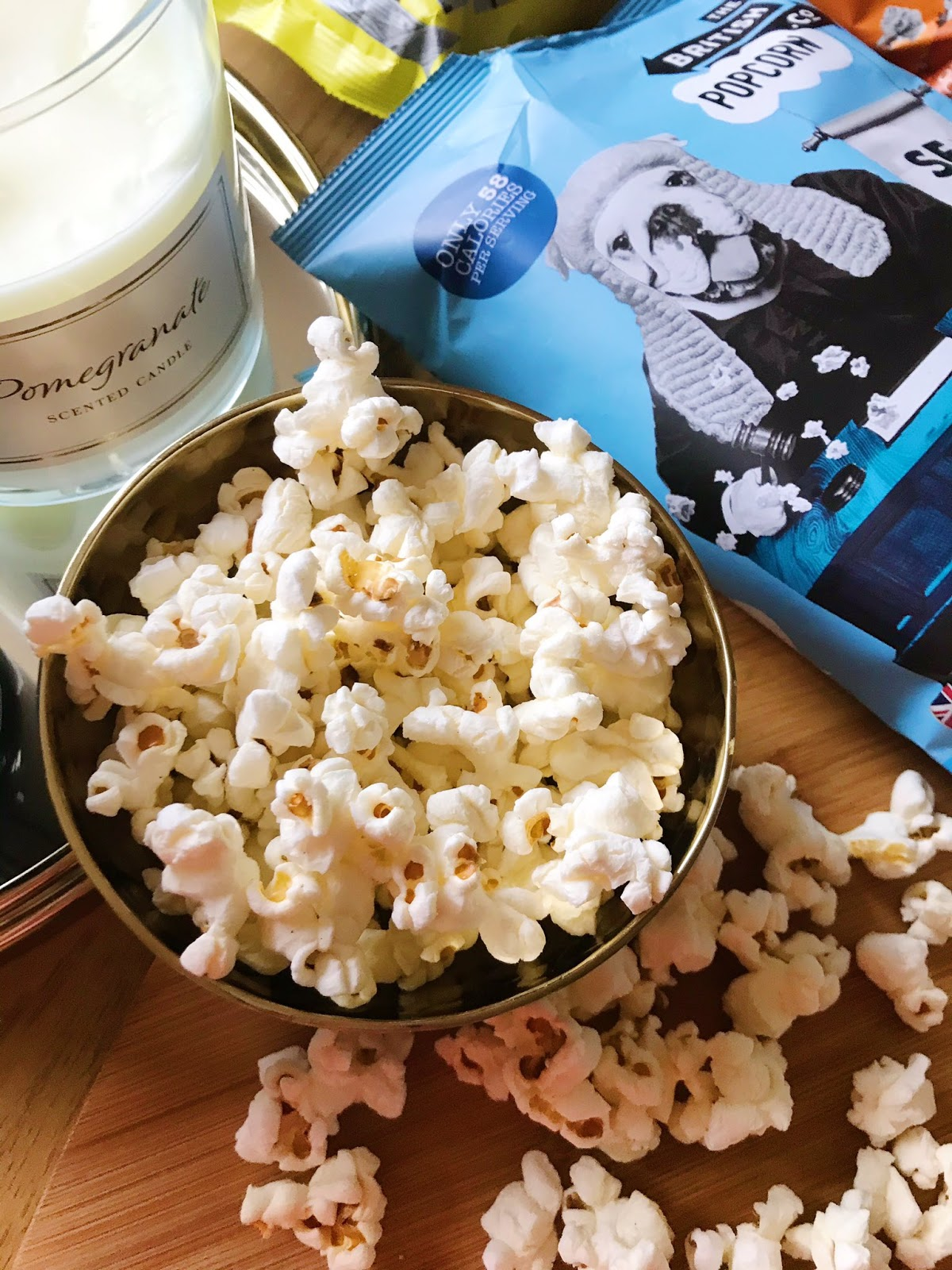 bags of popcorn from The British Popcorn Co, salted popcorn in gold bowl on chopping board
