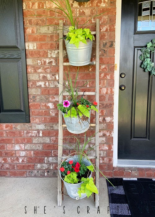 Vintage Wooden Ladder displaying galvanized buckets full of flowers.