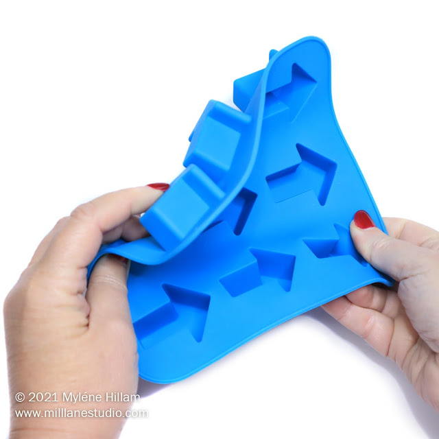 Two hands flexing a blue silicone arrow ice cube tray