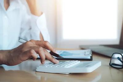 Foto de uma pessoa sentada, utilizando uma calculadora branca pequena, apoiada sobre uma mesa de madeira natural, segurando uma caneta metálica calculando o valor da multa na locação de imóveis