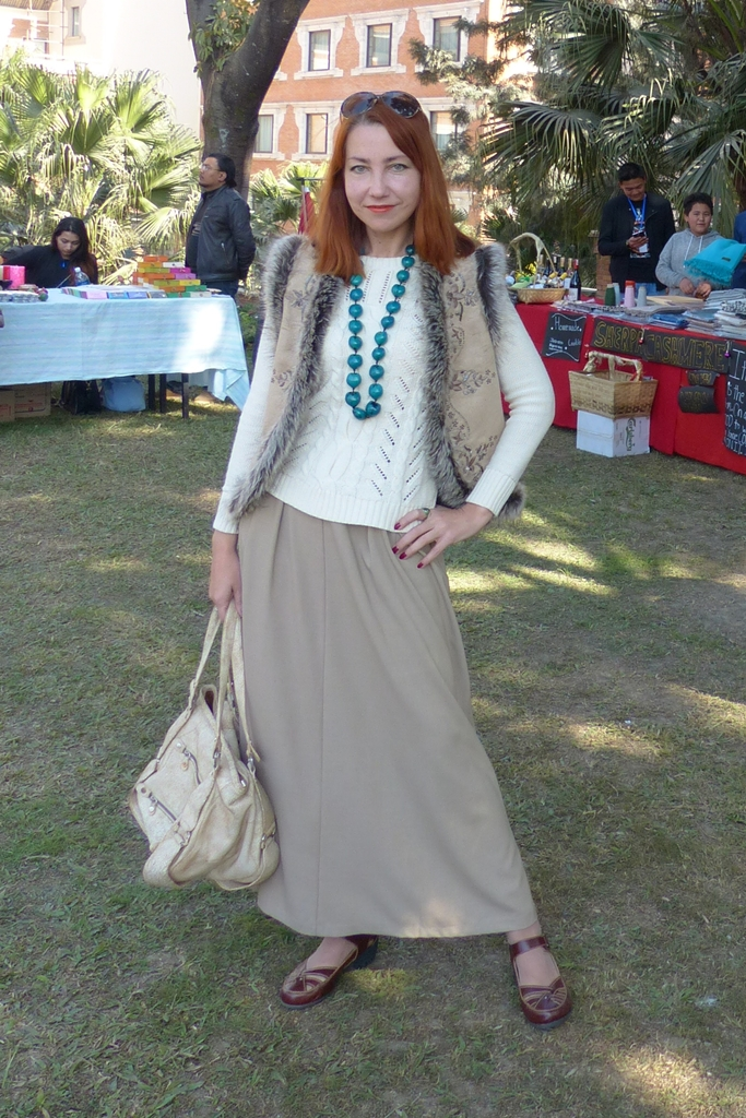 Fur trimmed vest worn with sweater, maxi skirt and beads
