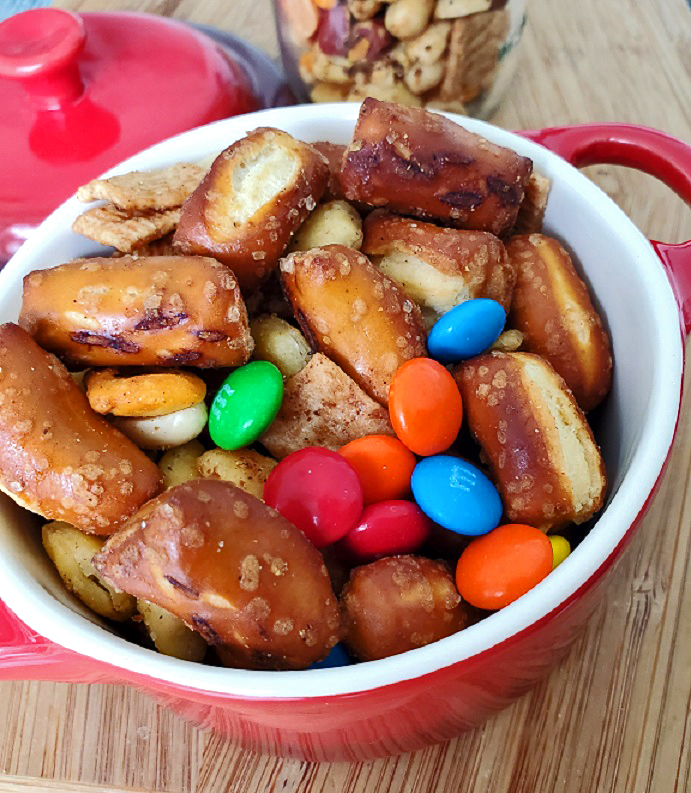 this is a red casserole bowl full on pretzel, cracker snack mix with nuts and candy
