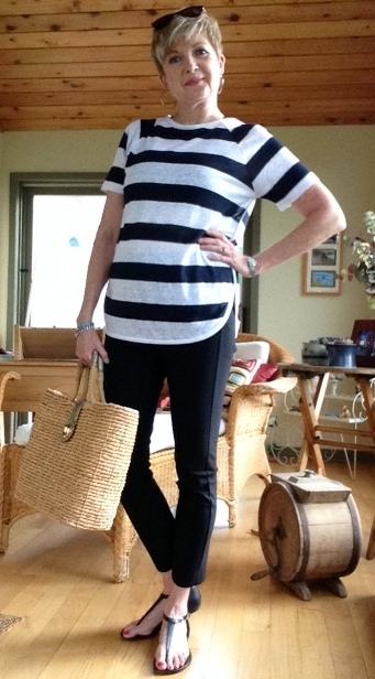 Woman in black pants, striped top, holding a straw tote bag.