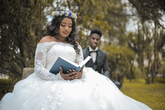 A bride holding a Bible with bridegroom behind