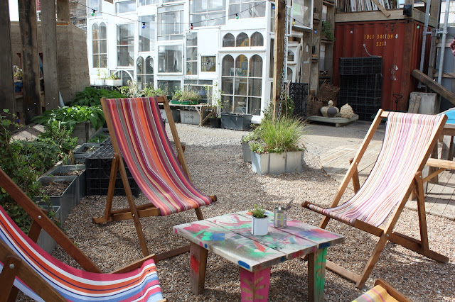 Skip Garden courtyard with deck chairs and table. Reclaimed window glass house in the background