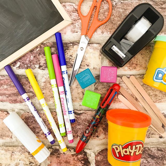 School supplies, tape, pens, scissors and crayons laid out