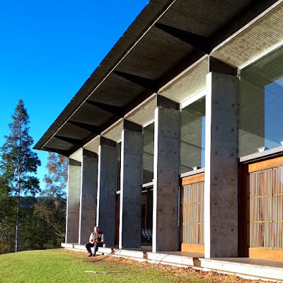 A man sitting on the ledge along the front of the main block of the Boyd Education Centre in front of an open sliding door.