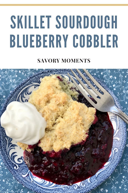 Sourdough blueberry cobbler on a serving plate with whipped cream.