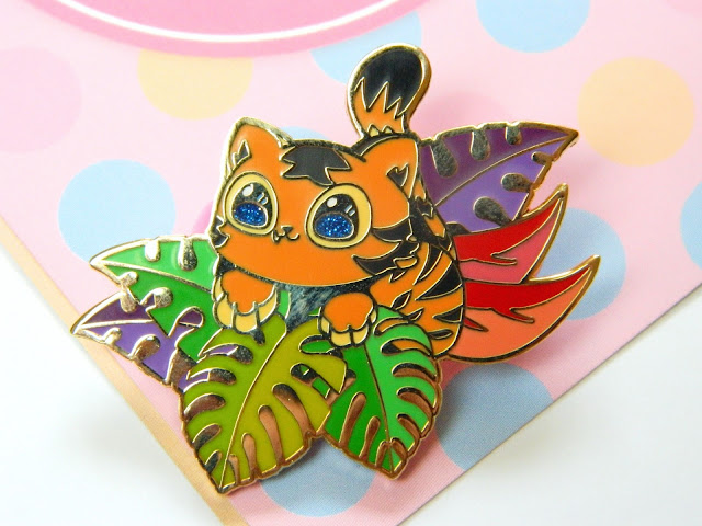 A pin badge of a cute tiger cub sitting in a bunch of colourful leaves