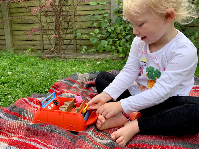 Putting mummy pig's sun hat in the boot of the Peppa Pig toy car